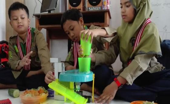 Para murid SD Muhammadiyah Pucang memamerkan robot pemotong buatannya (Solopos)