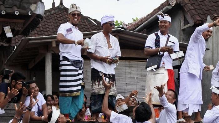 Mengintip Potret Keseruan Tradisi Lempar Uang di Bali